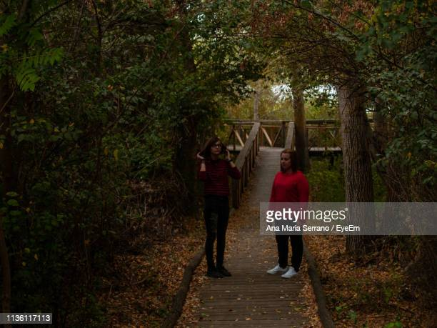Female Friends Standing Amidst Trees In Forest