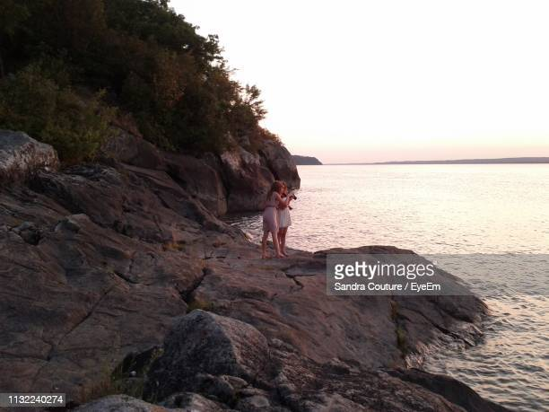 female friends standing at beach during sunset - lévis quebec stock pictures, royalty-free photos & images