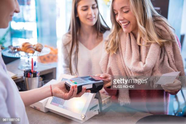 female friends standing at counter in cafe, paying using credit card - contactless payment stock pictures, royalty-free photos & images