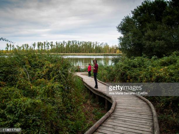 Female Friends Standing On Boardwalk Amidst Plants At Lakeshore Against Cloudy Sky