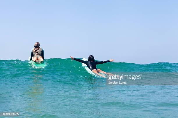 Female friends surfing, Hermosa Beach, California, USA