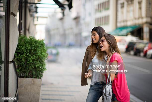 Female friends surprised at store window