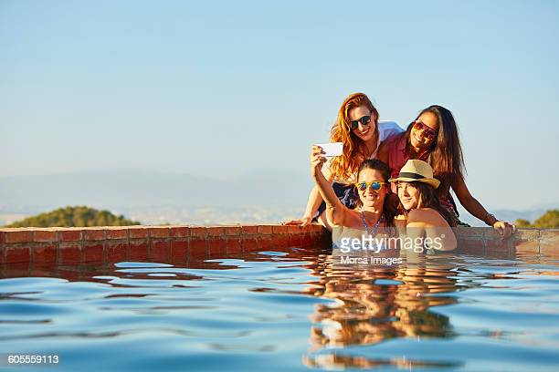 female friends taking self portrait at pool's edge - only young women stock pictures, royalty-free photos & images
