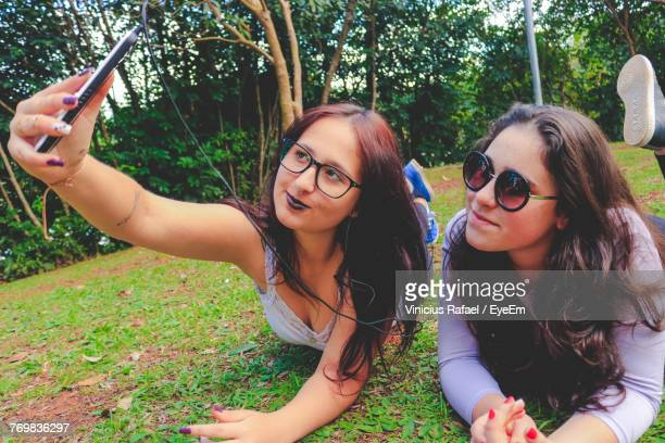 Female Friends Taking Selfie While Lying On Grass At Park