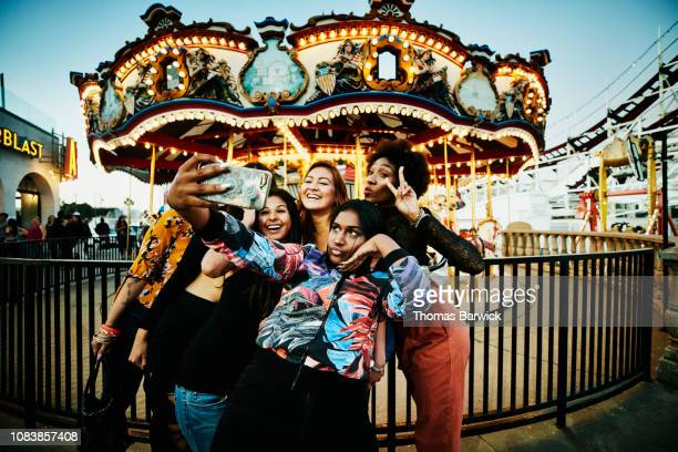 Female friends taking selfie with smart phone in front of carousel at amusement park