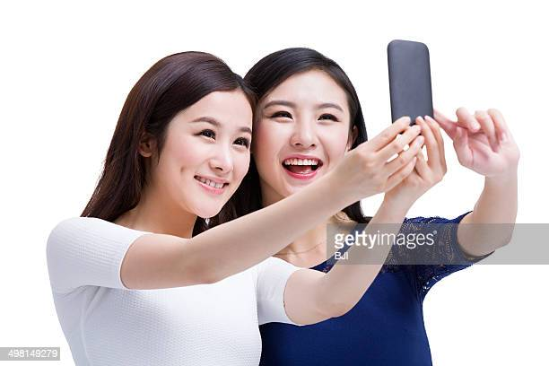 Female friends taking selfie with smart phone