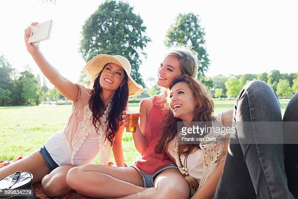 Female friends taking smartphone selfie at park party