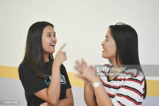 female friends talking against wall - jeffrey roque stock photos and pictures