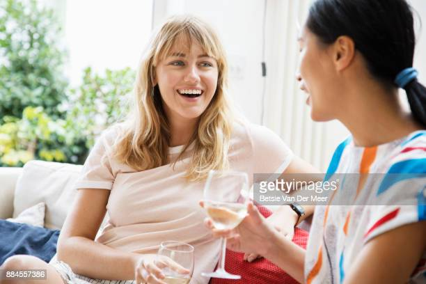 Female friends talking and laughing , sitting on sofa.