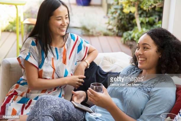 Female friends talking, sitting on sofa.