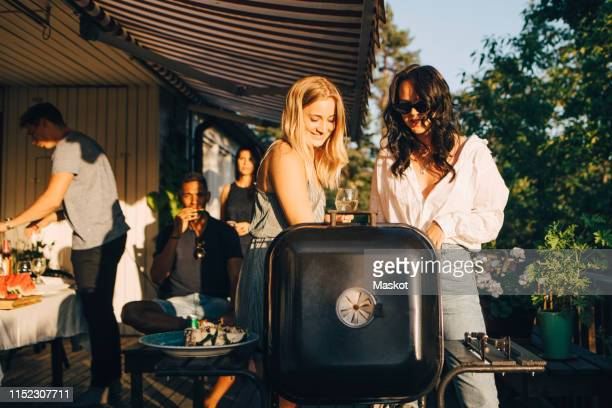 female friends talking while grilling food on barbecue in dinner party - barbecue social gathering stock pictures, royalty-free photos & images