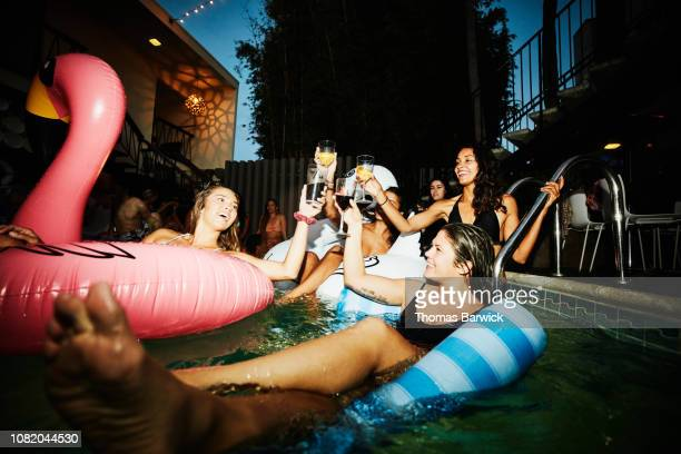 female friends toasting while floating in hotel pool during party - nachtleben stock-fotos und bilder