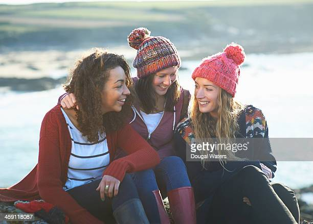 female friends together on coastline. - dougal waters stock pictures, royalty-free photos & images