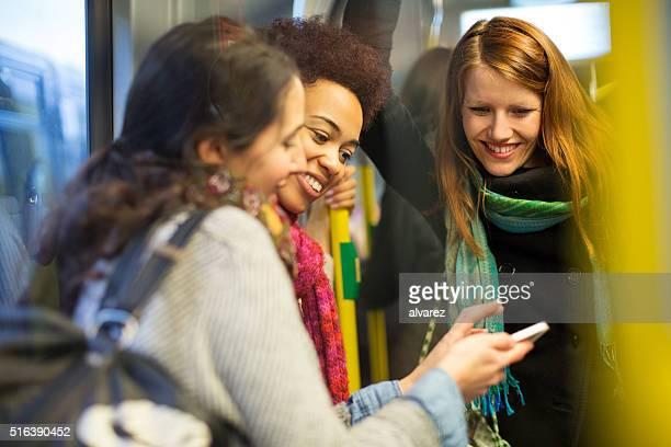 freundinnen, die mit dem zug mit mobiltelefon - u bahnzug stock-fotos und bilder