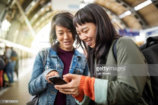 female friends using mobile phone at railroad station - 可動性 ストックフォトと画像