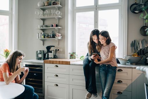 Female friends using mobile phone in kitchen at home - gettyimageskorea