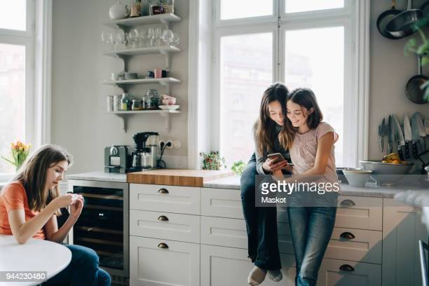 Female friends using mobile phone in kitchen at home
