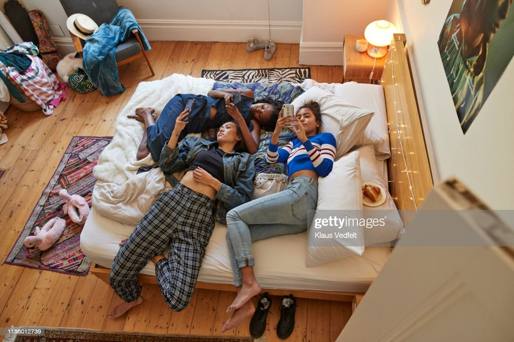 Female friends using phones while relaxing on bed : Stock Photo