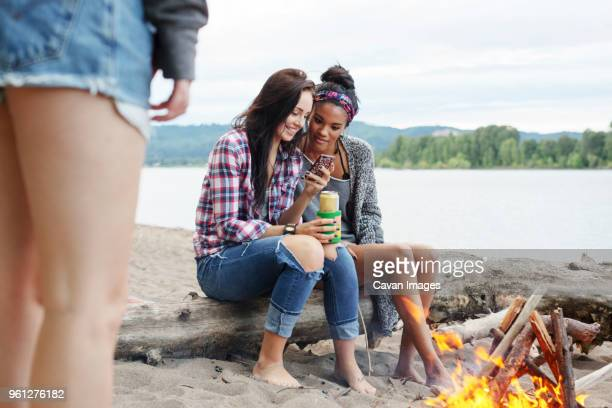 Female friends using smart phone while sitting on tree trunk by campfire against river