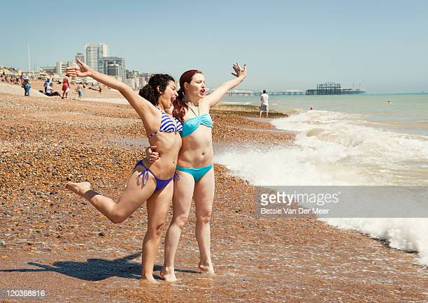 Female friends waiting for waves on shoreline.