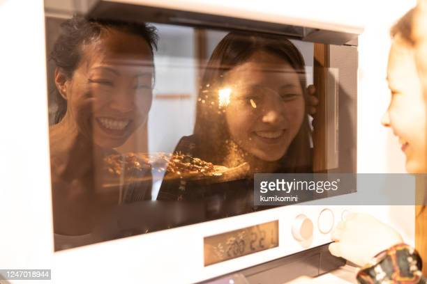 female friends waiting in front of oven - pizza stock pictures, royalty-free photos & images