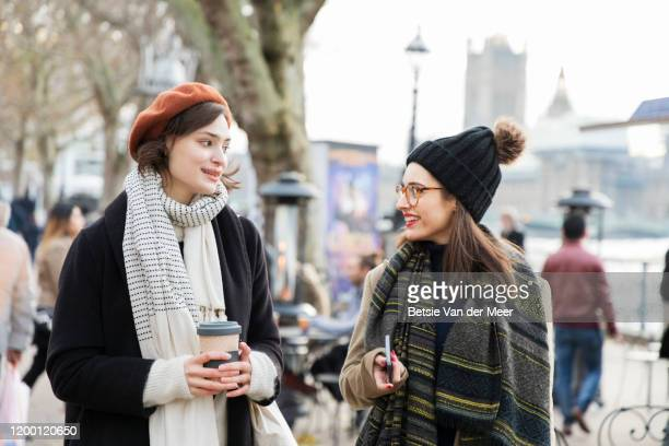 female friends walking at embankment river thames. - scarf stock pictures, royalty-free photos & images