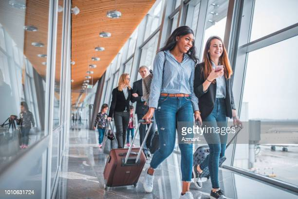 Female friends walking by window at airport