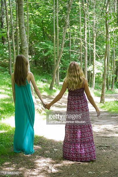 female friends walking hand in hand on path through woods - long dress stock pictures, royalty-free photos & images