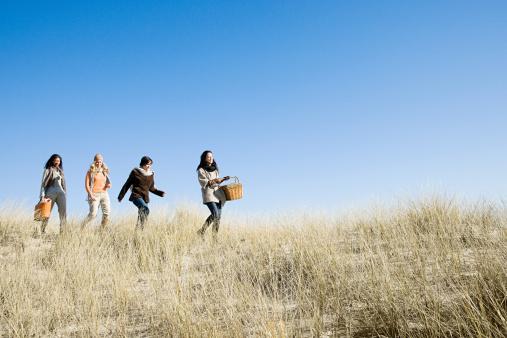 Female friends walking in marram grass - gettyimageskorea