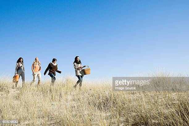 Femininos amigos andar no Feno-das-areias