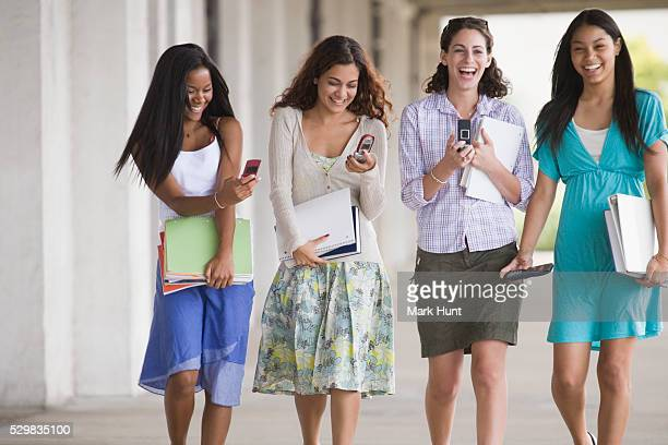 female friends walking in university corridor and using mobile phones - indian college girls ストックフォトと画像