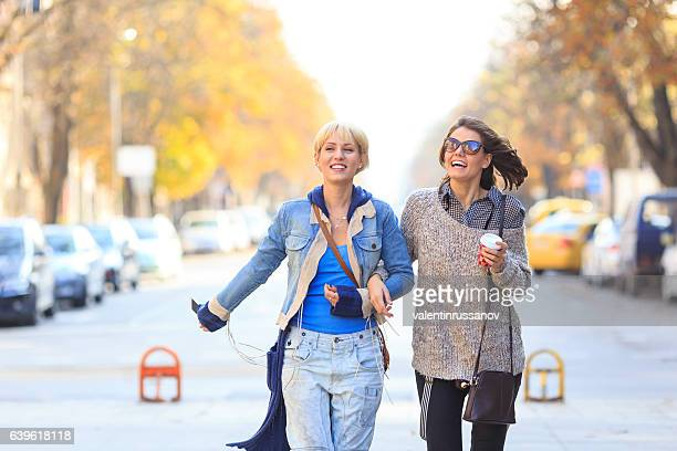 Female friends walking on street and holding hands