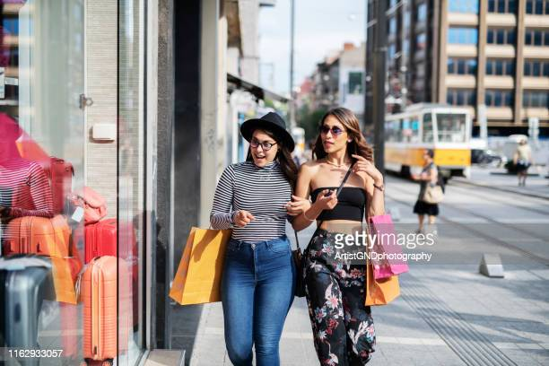 female friends walking on the shopping street and carrying shopping bags. - fashion show stock pictures, royalty-free photos & images