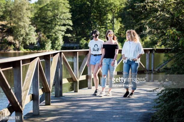 Female friends walking through park
