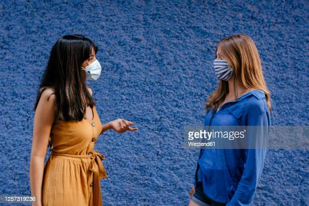 female friends wearing masks talking while maintaining distance against blue wall in city - female friendship stock pictures, royalty-free photos & images
