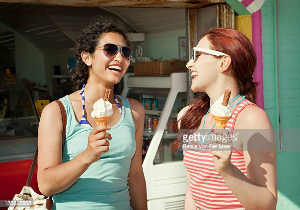female friends with icecreams in front of shop. - ice cream parlour stock pictures, royalty-free photos & images
