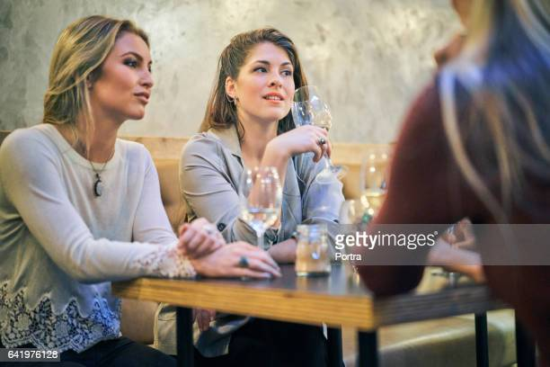 Female friends with wine looking away in bar