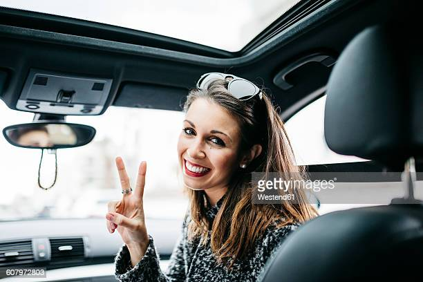Female front passanger in car making victory sign