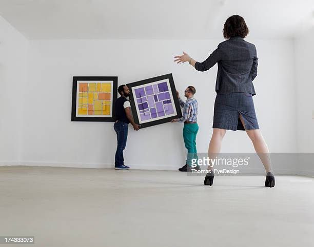 Female Gallery owner hanging a picture
