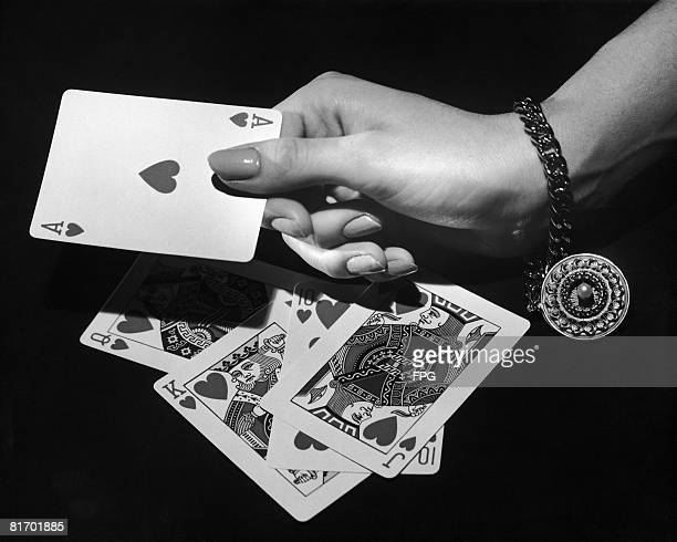 A female gambler produces a royal flush the highest ranking poker hand circa 1950