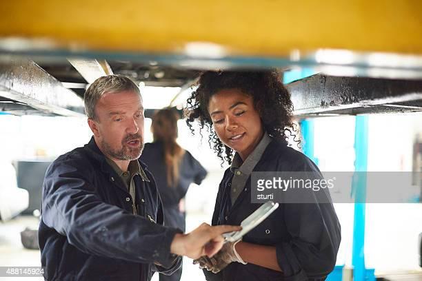 Weibliche Mechaniker mit Ihrem Chef garage