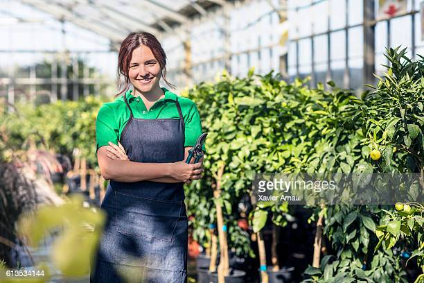 female garden center worker with pruners - pruning shears stock photos and pictures