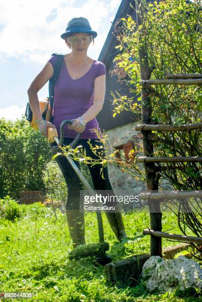 Female Gardener Cutting Grass With  Weed  Trimmer