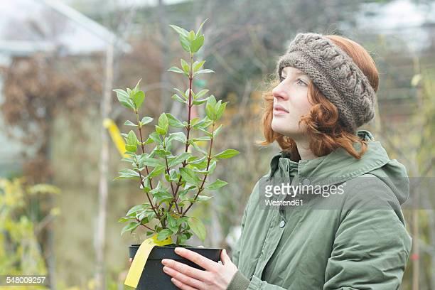 Female gardener holding flowerpot with a plant