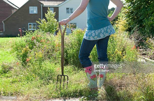 female gardener in overgrown residential garden