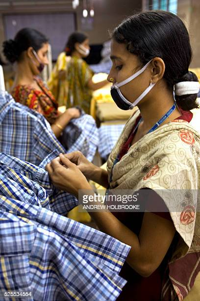 Female garment factory worker in Chittagong do the finishing work on shirts being manufactured for the American owned company, Wal-Mart. U.S....