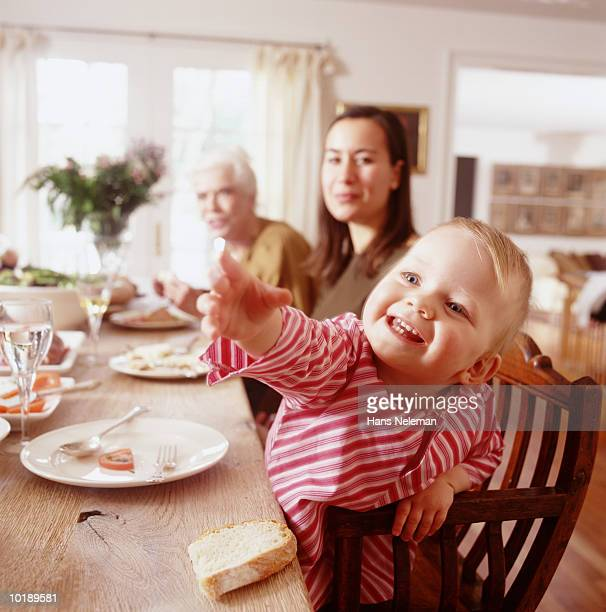 female generational family at dinner table, girl (2-4 years) reaching - 30 39 years photos et images de collection