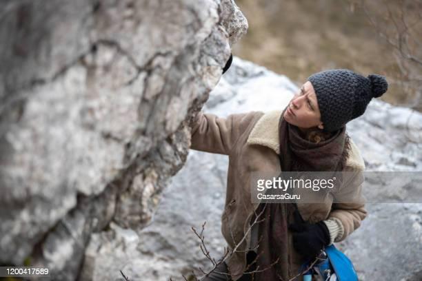 female geologist examining a boulder in mountains - geologia imagens e fotografias de stock