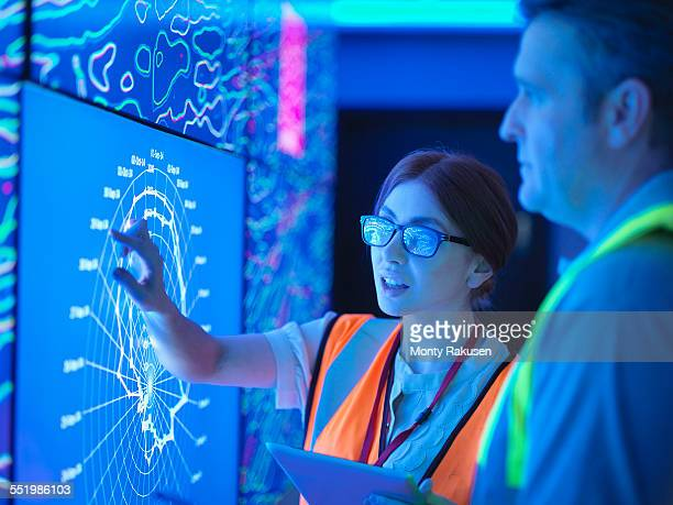female geologist with colleague studying graphical display of oil and gas bearing rock on screens - engineering stock pictures, royalty-free photos & images