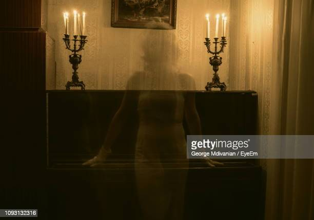 female ghost against piano in darkroom - ghost stock pictures, royalty-free photos & images